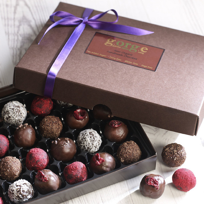 kakaomasse verschmelzen und als toping verwenden schachtel mit pralinen violettfarbe schleife deko geschenkidee zu jedem anlass