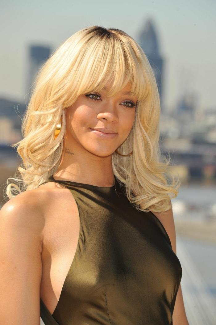 Rihanna mit blonden Haaren, Frisur mit Pony, matte Lippen und dezentes Augen Make-Up, olivgrünes Abendkleid