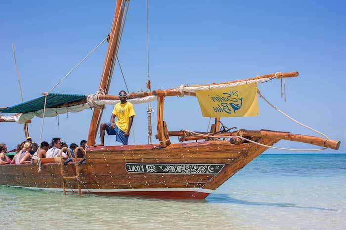 sansibar karte bild von einem boot das zum safari blue fährt wassersafari reiseleiter mann mit gelbem t-shirt
