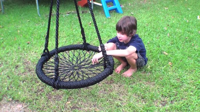 ein Junge auf einer Wiese spielt mit einer schwarzen Schaukel - Kinderschaukel für Garten