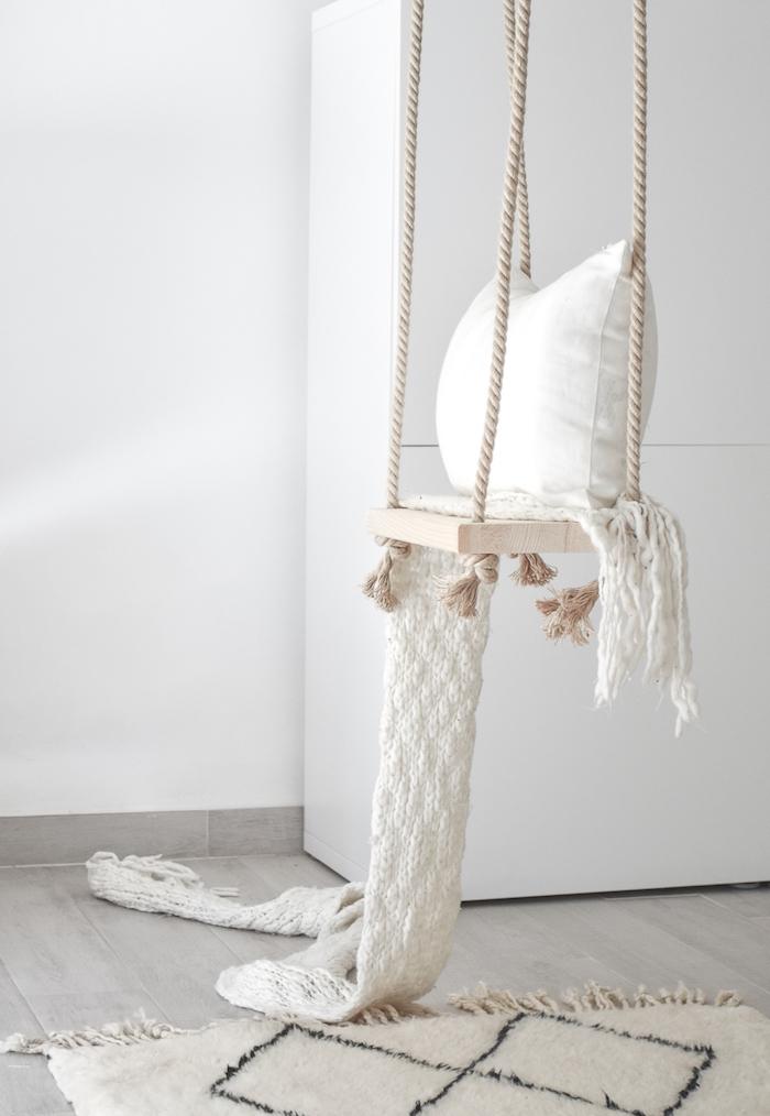 Schaukelgestell - eine weiße Schaukel im Wohnzimmer, ein weißer Teppich und weiße Wände