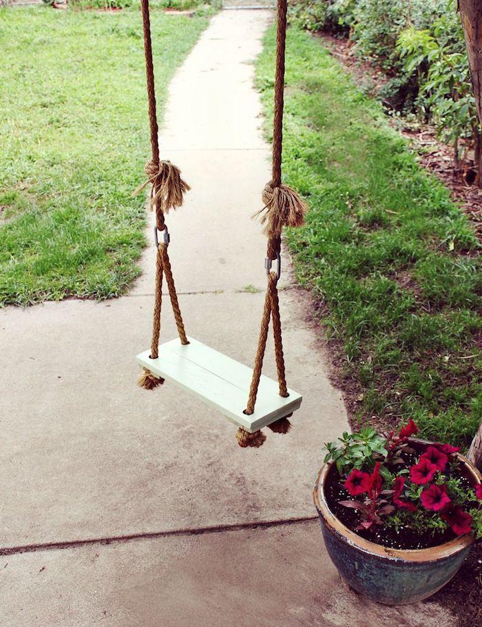 eine kleine Schaukel aus Seil und Holz - Baum als Schaukelgestell, neben rote Blumen