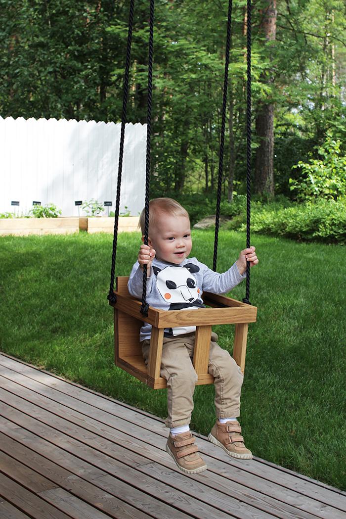 Kinderschaukel im Garten für ein süßes Baby, das gern geschaukelt wird