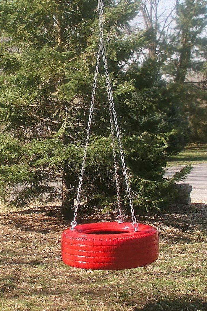 eine Schaukel aus einem roten Reifen mit drei Ketten befestigt in Garten mit vielen Bäumen