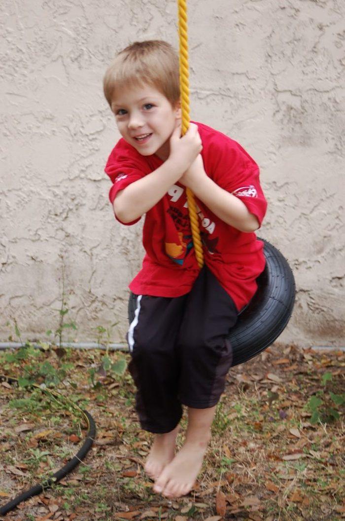 eine einfache Schaukel bauen aus Reifen und Seil, Junge mit einem Traininganzug