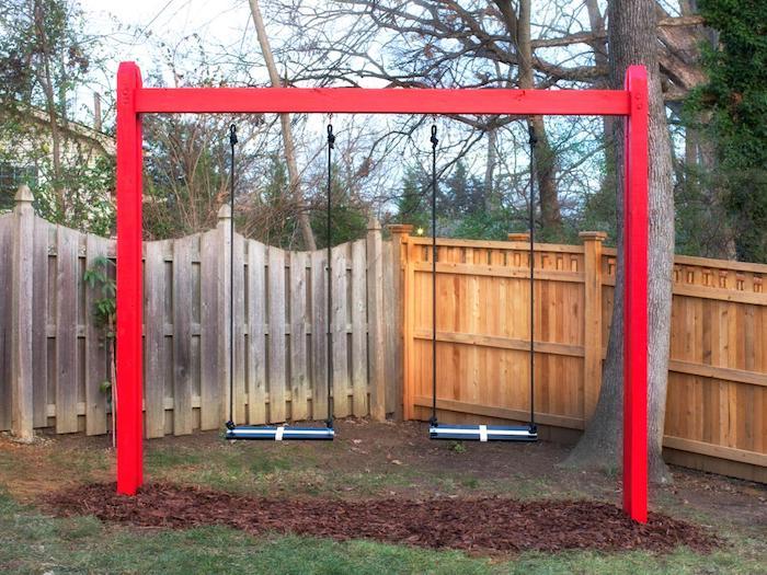 eine rote Kinderschaukel im Garten mit schwarz und weiße Sitzplätze und Seile zur Unterschützung