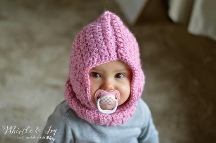 Selbstgestrickte rosafarbene Kapuze, schönes Geschenk zur Geburt selber machen, süßes Baby mit großen schwarzen Augen
