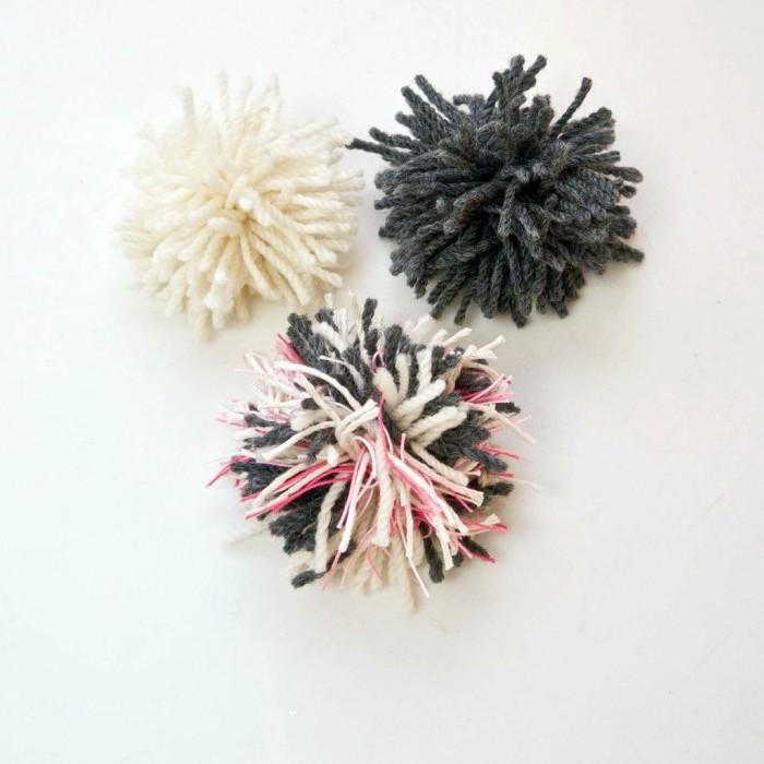 drei Pompoms in schwarzer, weißer und rosa Farbe - schnell und einfach Katzenspielzeuge basteln