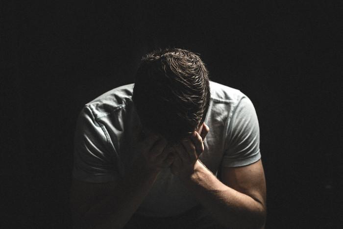 trauriges bild mit einem traurigen mann, der weint, und mit einer schwearzen wand - traurige bilder zum weinen