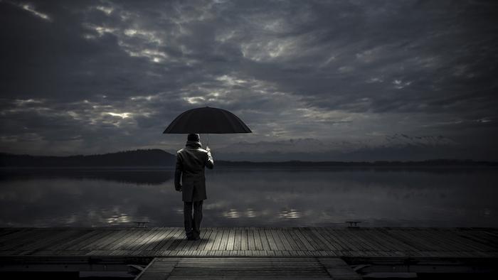 noch ein trauriges bild mit einem einsamen mann mit einem schwarzen regenschirm . meer und himmel mit grauen und schwarzen wolken - traurige bilder zum weinen