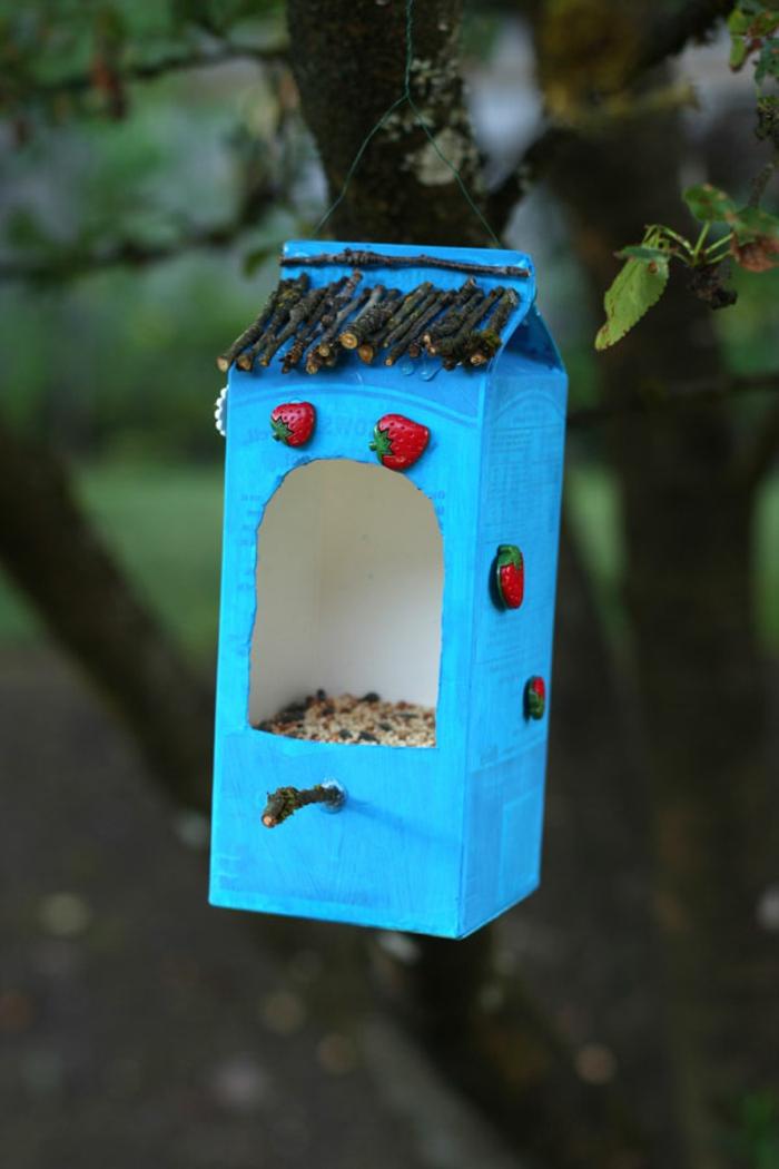 Vogelfutterhaus aus Milchkarton selber basteln, mit kleinen Erdbeeren aus Keramik und Stäbchen verzieren
