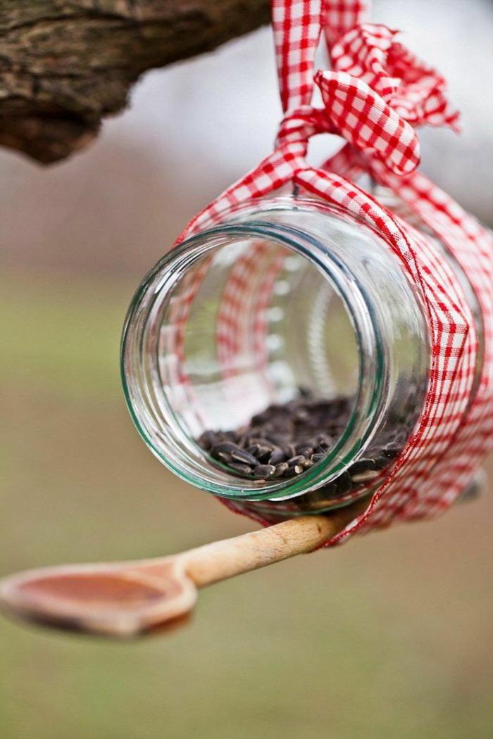 Nistkasten sehr einfach selber machen, aus Einmachglas, Holzlöffel und Band, mit Sonnenblumenkernen befüllen