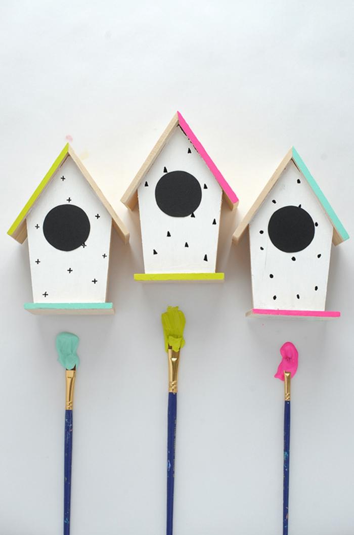 drei Futterhäuschen für Vögel aus Holz, weiße Wände mit Punkten, Kreuzen und Dreiecken verziert, bunte Dächer
