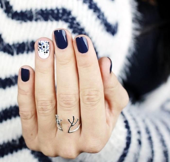 Winterliches Nageldesign in Dunkelblau und Weiß mit Punkten, ovale Nagelform, kuscheliger Pullover im Hintergrund