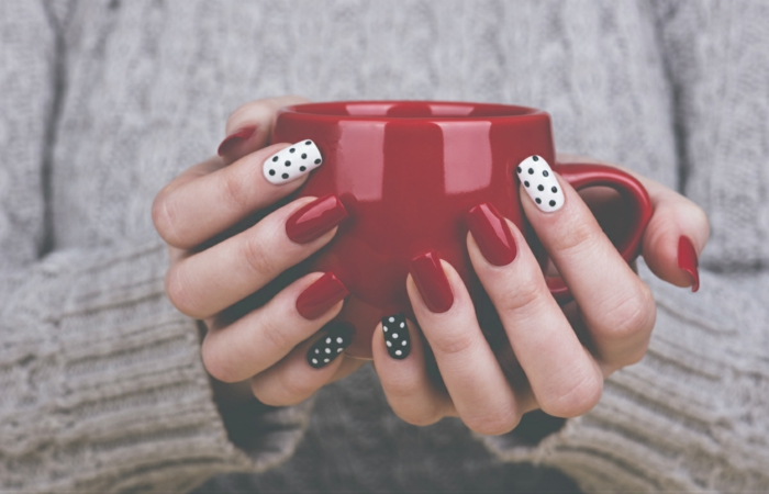 Winternägel zum Nachstylen, schwarze Punkte auf weißem Grund und weiße Punkte auf schwarzem Grund, rote Porzellantasse, kuscheliger Pullover im Hintergrund