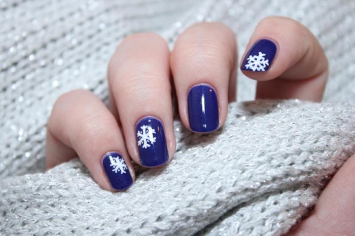 Weiße Schneeflocken auf dunkelblauem Grund, ovale Nagelform, schöne Idee für Winternägel zum Nachstylen