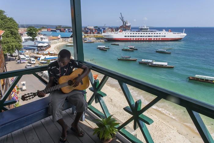 sansibar stadt schönes ambiente in tansania mann einheimischer spielt gitarre auf der terrasse wasser schiff aussicht oben über das wasser
