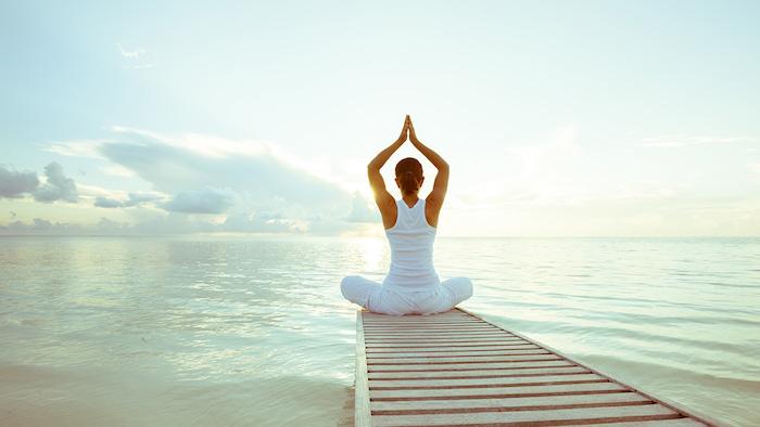 Yoga beim Sonnenuntergang am Meer treiben, grün-weißes Meereswasser, Arme Richtung Himmel strecken