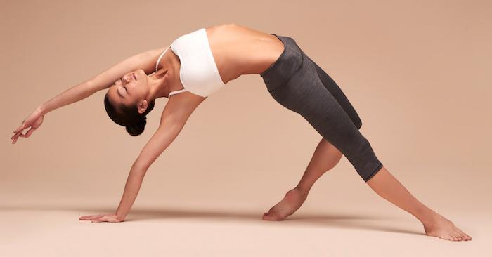 Stretchposition für Fortgeschrittene, kurzes sportliches Top mit Trägern in Weiß, 7/8 Hose, beige-rosa Hintergrund
