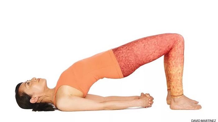 Yoga für Anfänger: asiatische Frau, die die Brückenposition übt, gestreckte Arme und geschlossene Hände, Füße am Boden, Rücken und Po in der Luft