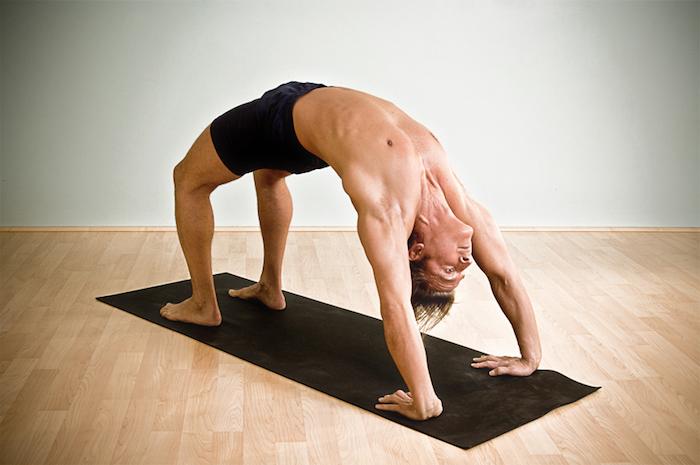 Mann, der die Brückenposition einnimmt, kurze schwarze Sporthose, graue Wand, Laminat, Mann mit mittellangen Haaren