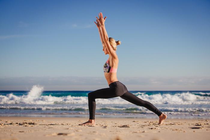 Yoga für Anfänger, Yoga am Strand treiben, Frau macht die Kriegerstellung, Meereswasser mit drei Farben