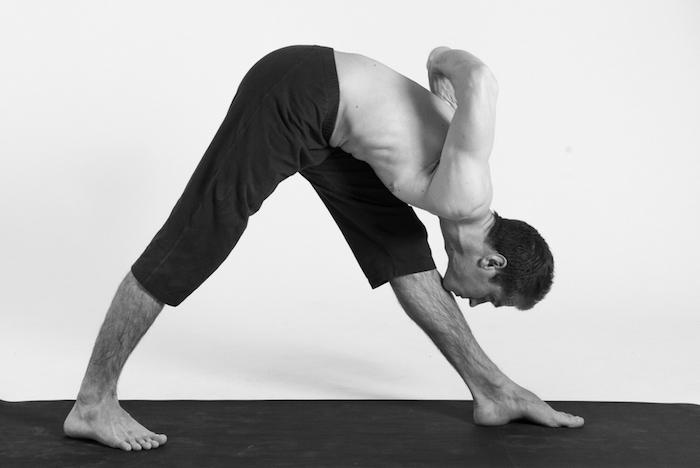 ein Mann macht Yoga, das Bein mit dem Kinn berühren, sich nach vorne lehnen, schwarz-weißes-Foto