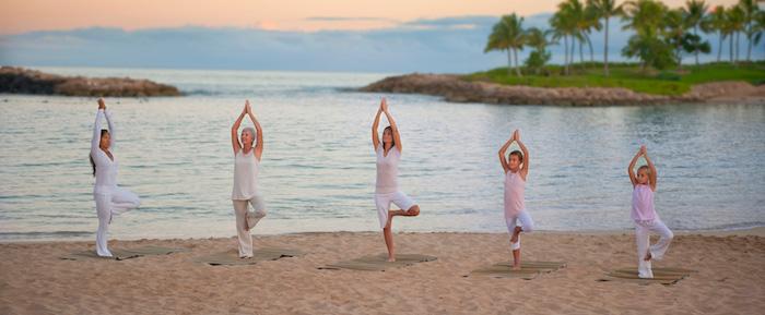 drei Frauen und zwei Kinder machen Yoga am Strand, zwei kleine Insel mit Palmen, Sonnenuntergang