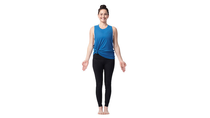eine Frau, die mit den Armen nach unten und die Handflächen nach vorne stillsteht, Zehen zueinander drücken, lächeln und weiße Zähne zeigen