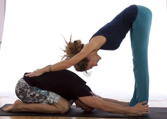 Trust Yoga für Liebespaare, Mann in Babyposition, Frau mit den Händen auf seinem Rücken, Hochsteckfrisur für sehr lange Haare