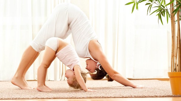 eine coole Mutter, die zusammen mit ihrer kleinen Tochter Yoga treibt, kleines Mädchen mit blonden Haaren, Gerdinen lang bis zum Boden