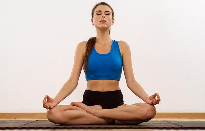 Yoga für Anfönger, eine junge Frau praktiziert Meditation im Yoga Studio mit weißen Wänden und Parkettboden, hübsche Frau mit leichter Schminke und kleinen Ohren, Sukhasana