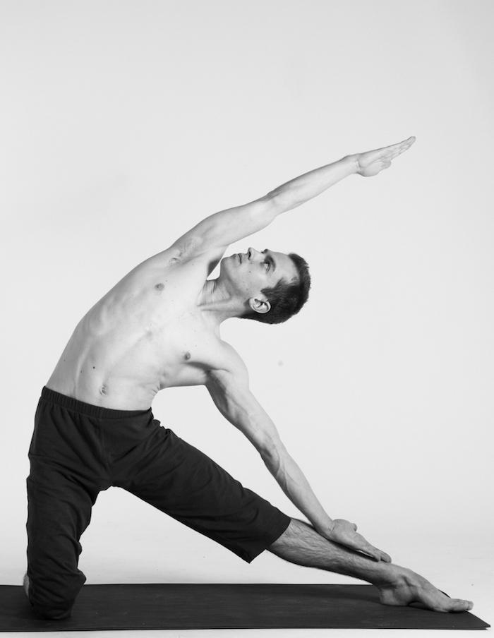 Parighasana Yoga Position, Mann mit gestrecktem linken Bein und Blick, gerichtet nach oben, schwarze Sporthose bis zum Knie