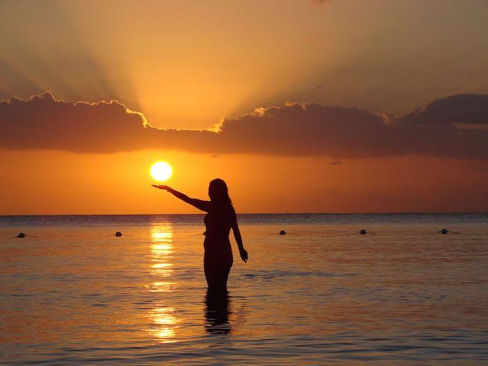 kreative bilder auf dem urlaub machen sansibar sonnenuntergang orange himmel frau macht fotos