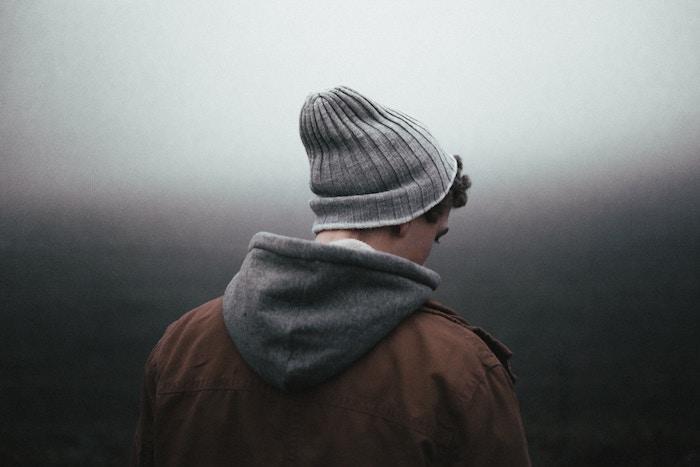 noch ein trauriges bild mit einem jungen traurigen mann mit jacke im nebel - zum thema traurige bilder und traurige sprüche zum weinen und nachdenken
