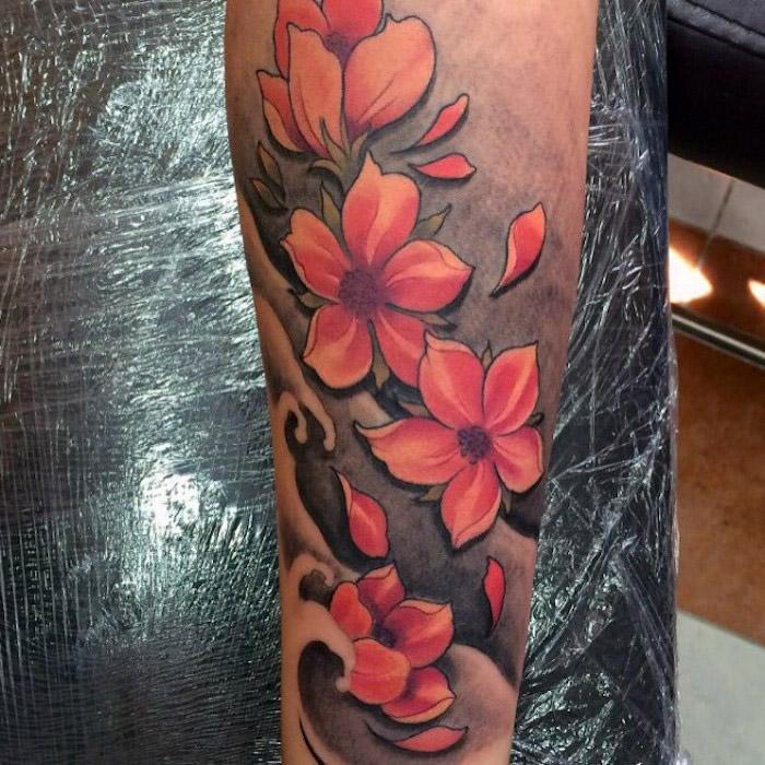 kirschblüten tattoo am unterarm, tätowierung mit wasserwellen und roten blüten