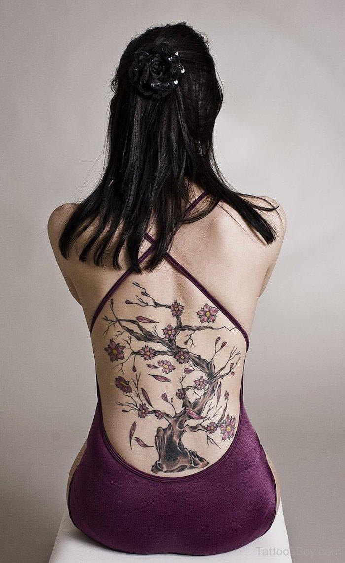frau mit schwarzen glatten haaren, lila kleid und kirschblüten tattoo am rücken