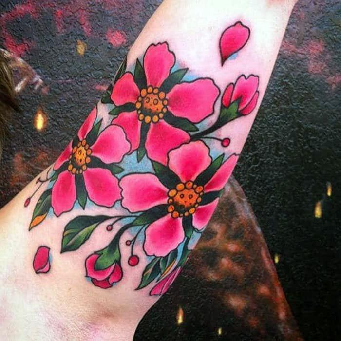blumenranke tattoo am oberarm, tätowierung mit rosa kirschblüten als motiv