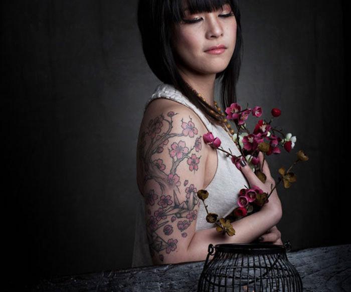 japanische tattoos für frauen, frau mit kurzen schwarzen haaren und kirschbraum tattoo am oberarm