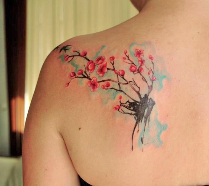 tattoos mit bedeutung, frau mit wasserfarben tattoo am rücken