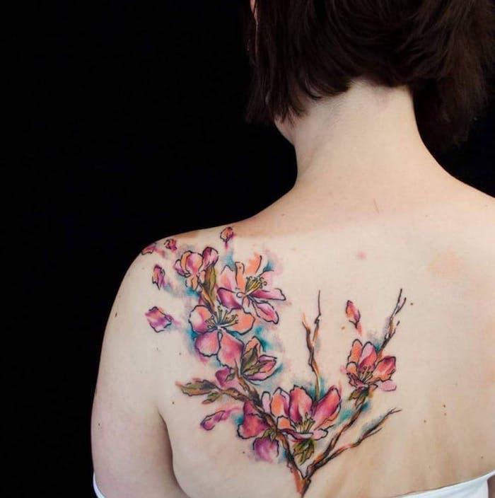 blumenranke tattoo am rücken, frau mit wasserfarben tattoo mit blumen motiv