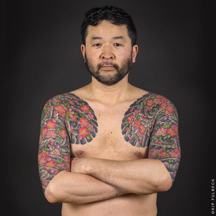 japanische tattoos, mann mit großen tätowierungen mit wasserwellen und kirschblüten