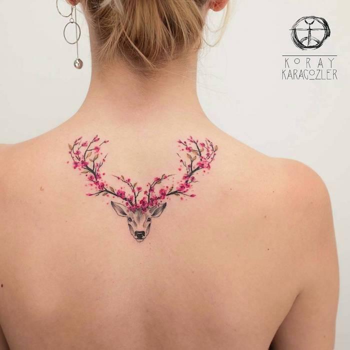 tattoo bedeutung, frau mit tattoo am rücken, hirsch mit gewieh aus kirschblüten