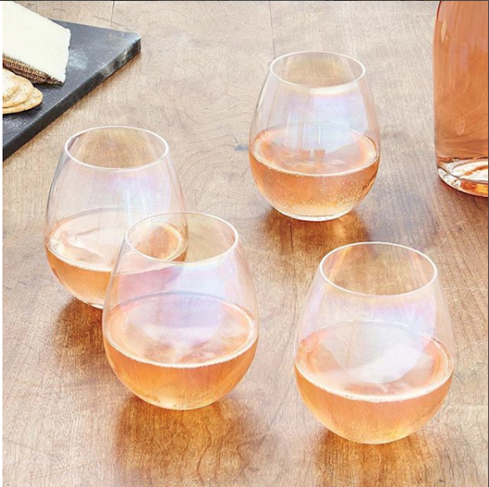 ein 4-Gläser-Set aus dünnem Glas, vier Gläser mit Obstsaft, Glasflasche mit Obstsaft, schwarze Servierplatte aus Marmor
