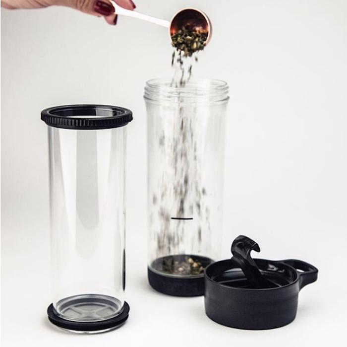 zwei transparente Plastikflaschen für Tee mit schwarzen Deckeln, ein großer Löffel aus Edelstahl, eine Frau mit rot lackierten Nägeln kocht Tee