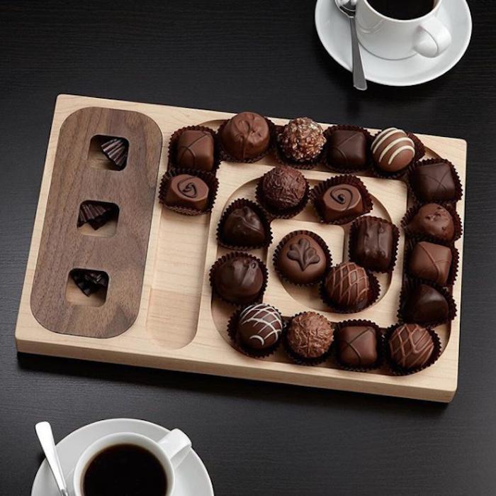 Servierplatte aus Holz mit schickem Design, Schoko Pralinen mit Milch- und Bitterschokolade, drei kleine quadratische Löcher, zwei weiße Porzellantassen mit schwarzer Kaffee, zwei Teelöffel auf einem schwarzen Tisch