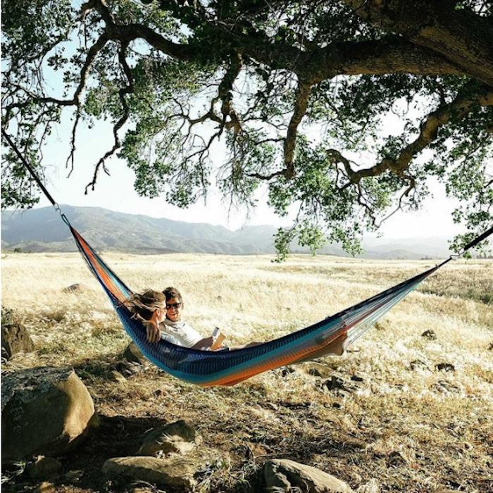 ein Mann mit mittellangen dunklen Haaren und dunklen Sonnenbrillen, der ein weißes T-Shirt trägt, und eine Frau mit langen dunkelblauen Haaren machen einen Ausflug und liegen in einer Hängematte, aufgehängt unter einem Baum, ein großer Baum mit schönen grünen Blättern, große Steine unter der Hängematte, Gebirgaussicht und gelbes Gras