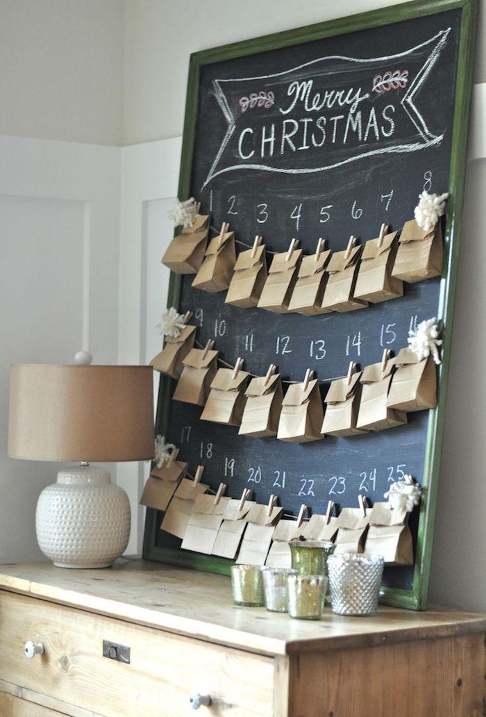 fünfundzwanzig kleine Tüten mit Wäscheklammern befestigt an einer schwarzen Tafel - Adventskalender für Männer