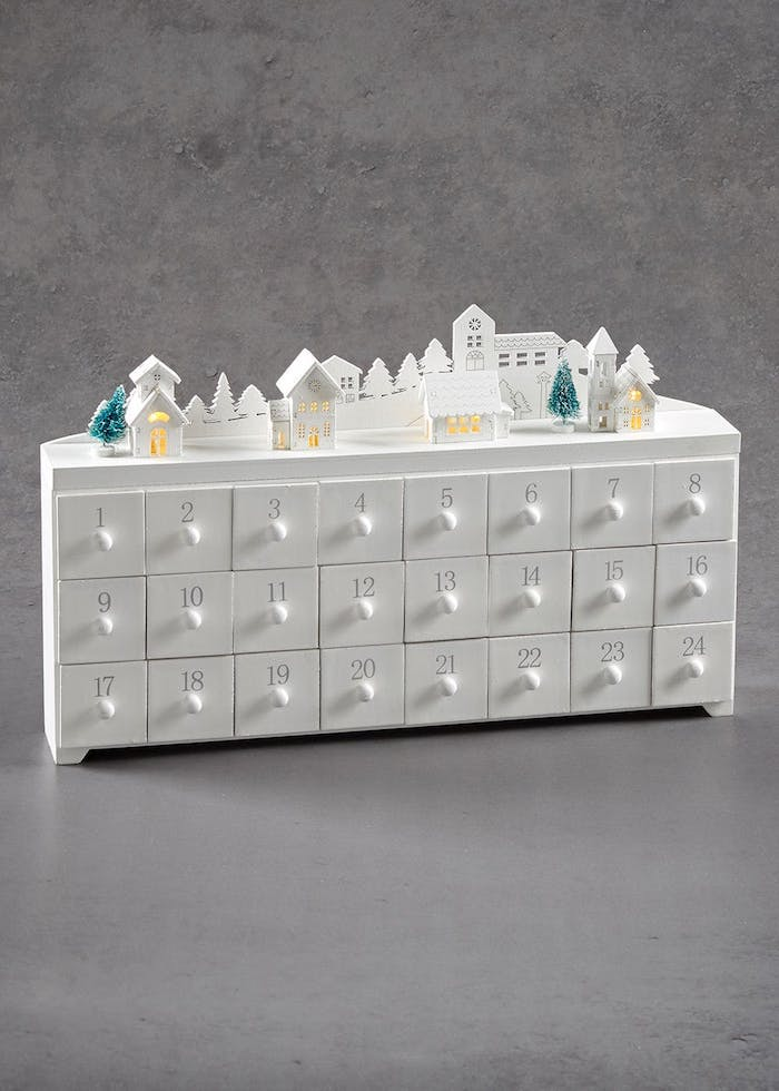 Adventskalender befüllen - ein winziger Kalender aus weißem Holz mit nummerierten Schubladen