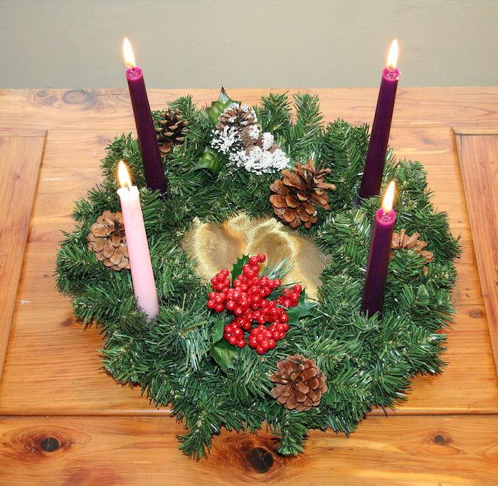 adventskranz mit lila kerzen und einer pinken kerze und ästen mit grünen blättern und braunen zapfen